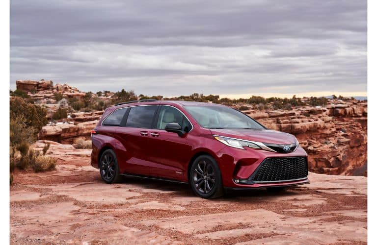 2021 Toyota Sienna XSE exterior shot with dark red paint color parked on a red rock cliff in a desert