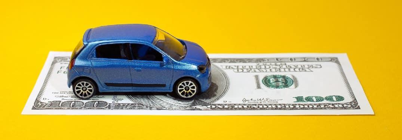 a tiny toy blue car parked on a hundred dollar bill symbolizes car credit
