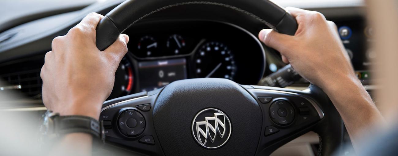 Hands on a black 2019 Buick Regal steering wheel