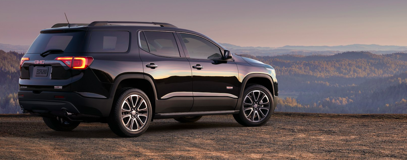 Black 2019 GMC Acadia overlooking valley with trees