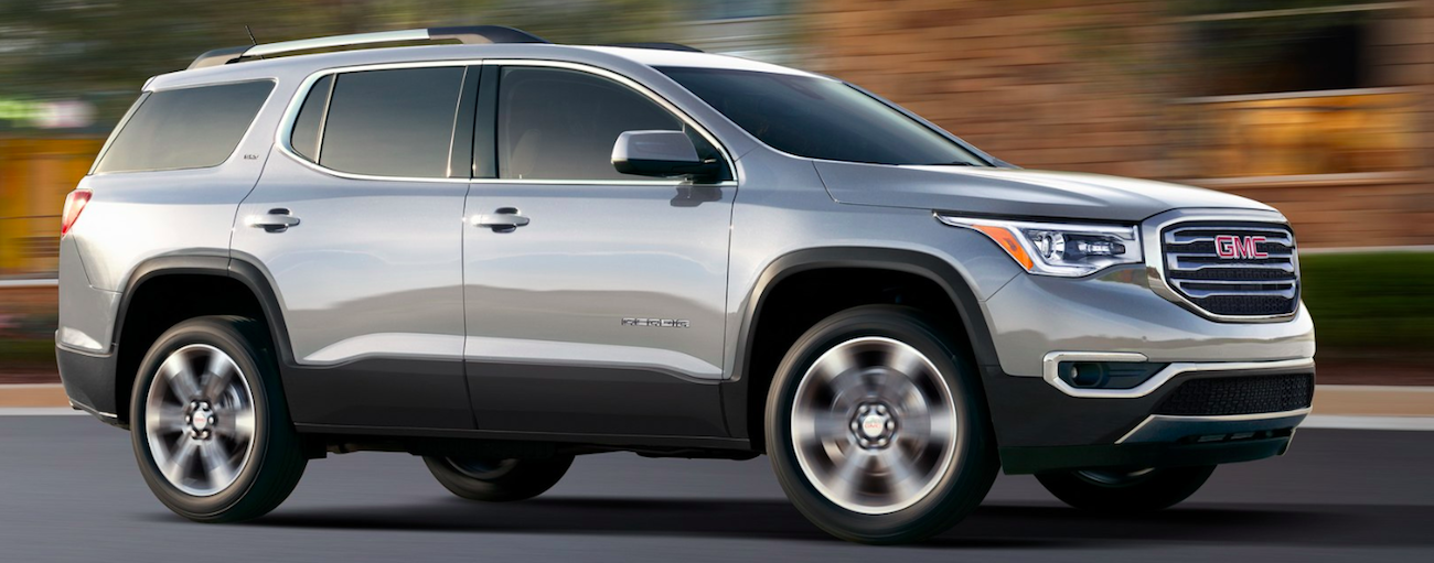 Gray 2019 GMC Acadia driving with out of focus background