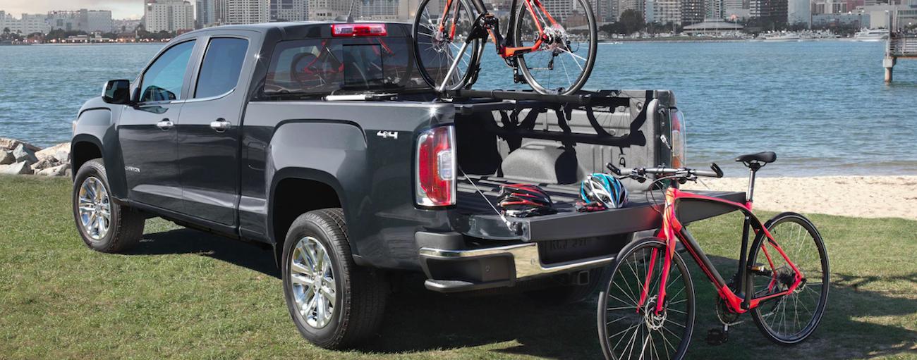 Black 2019 GMC Canyon unloading bikes near city river