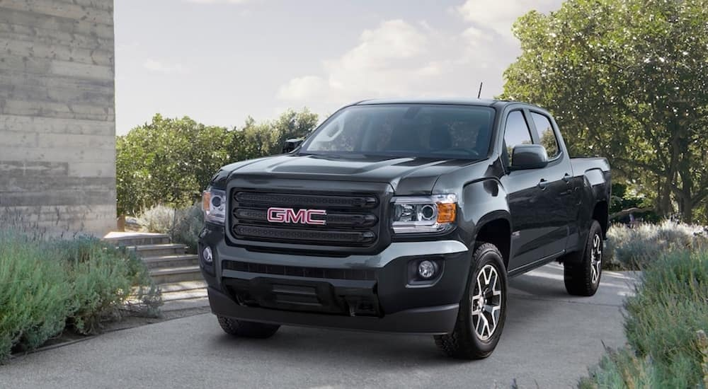 A black 2019 GMC Canyon parked in the driveway of a modern home