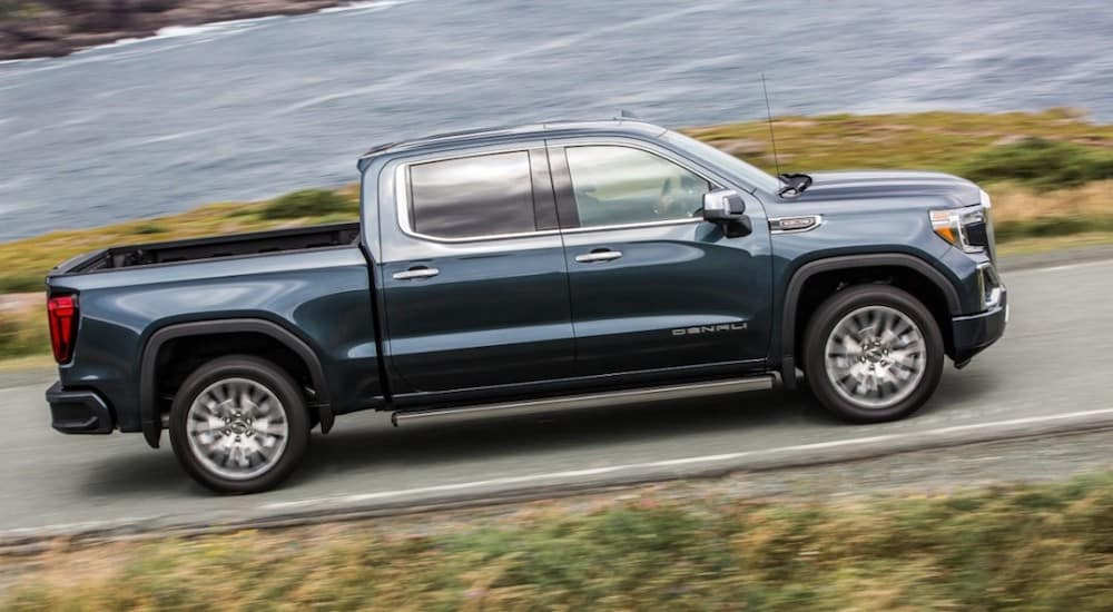 A dark blue 2918 GMC Sierra 1500 cruises a coastal road