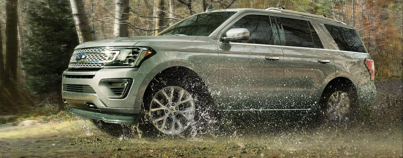 Silver 2019 Ford Expedition driving through mud in woods