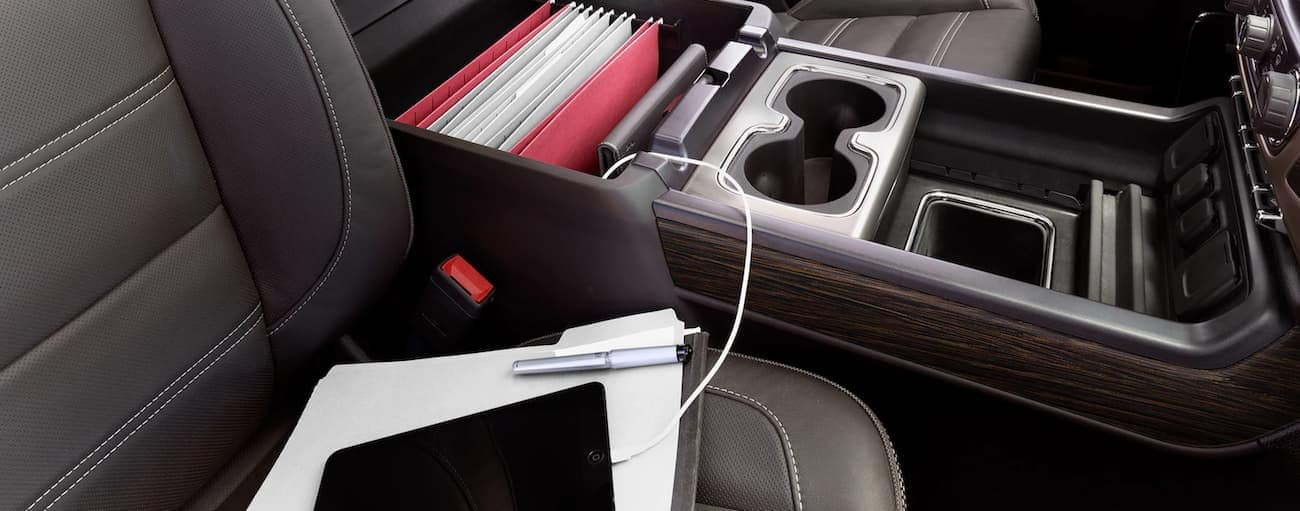 Storage compartment in 2019 GMC Sierra 3500HD center console, holding files, charging ipad