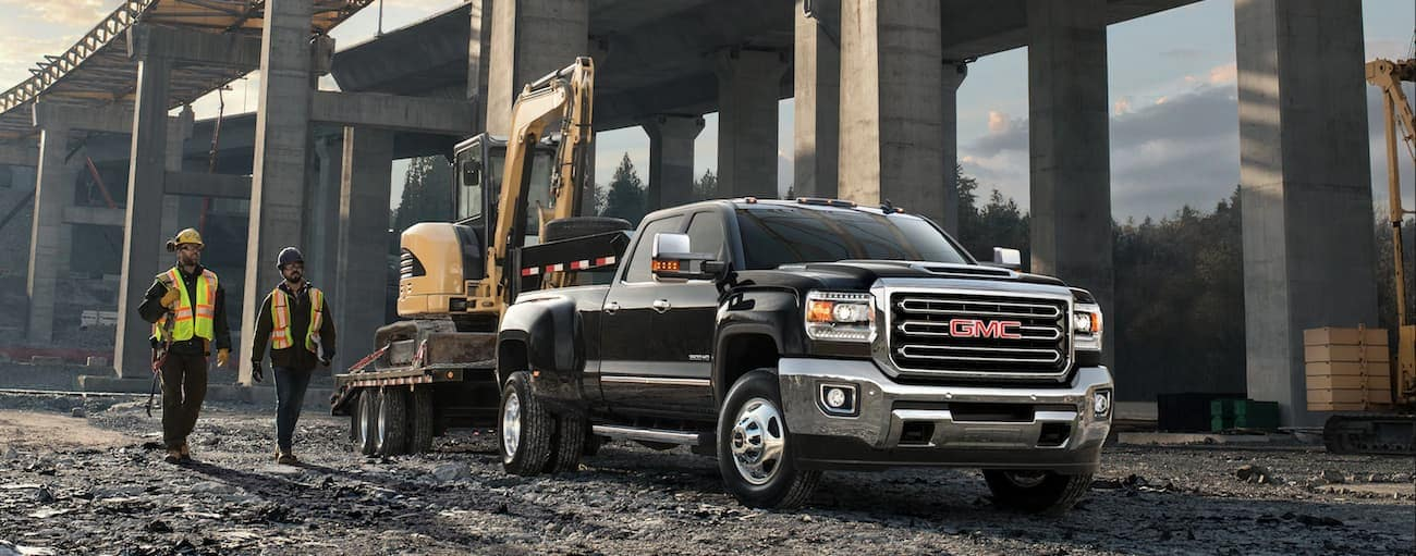 Black 2019 GMC Sierra 3500HD with tractor on trailer, construction workers