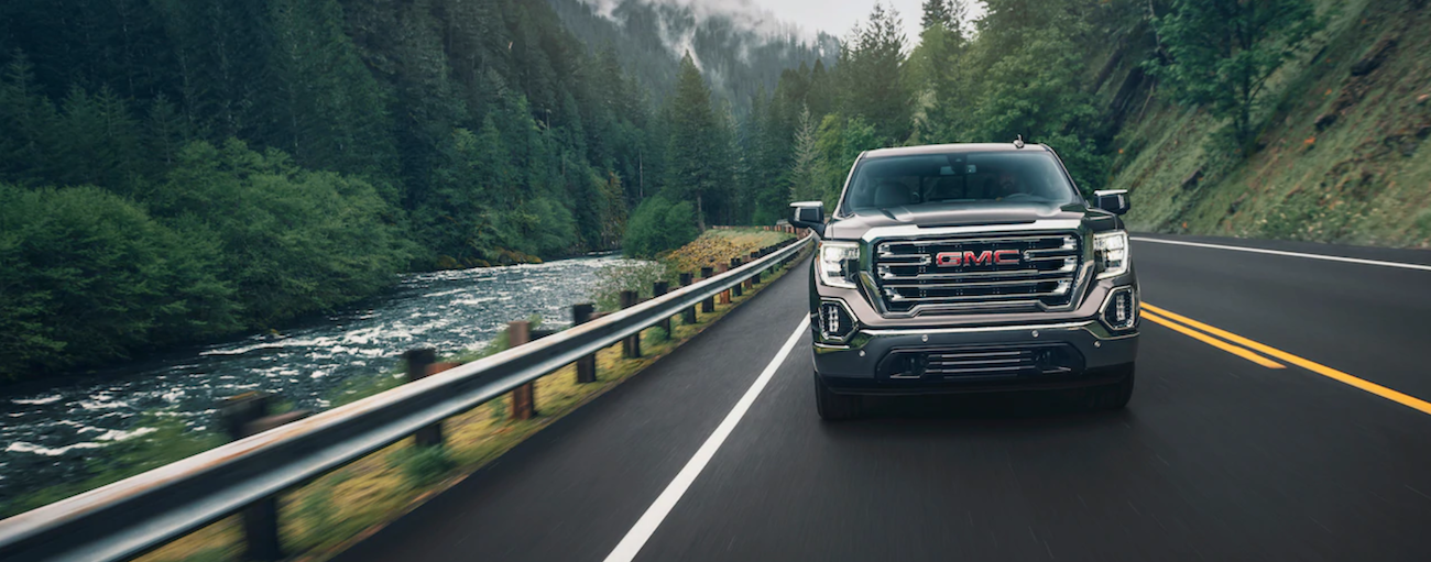 Black 2019 GMC Sierra 1500 driving towards camera next to woodland river
