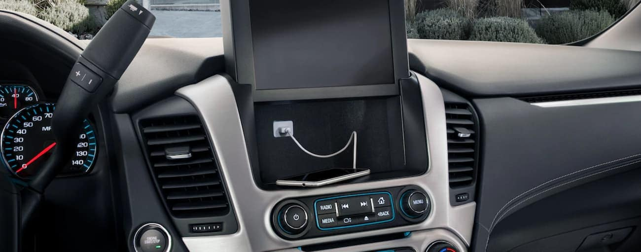 Raised touchscreen showing hidden compartment behind infotainment center in 2019 GMC Yukon
