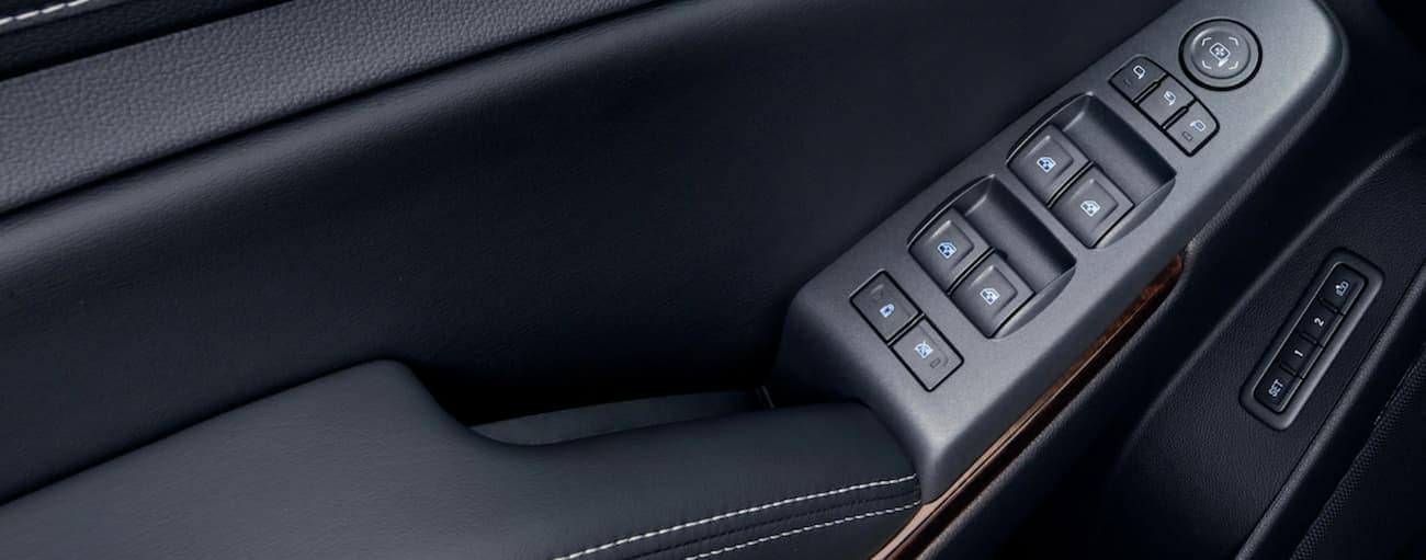 Black plastic and leather interior with wood accents of 2019 GMC Yukon, closeup of controls on door