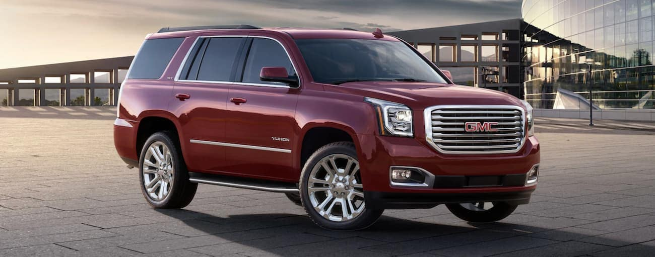 Dark red 2019 GMC Yukon in front of glass building at sunset
