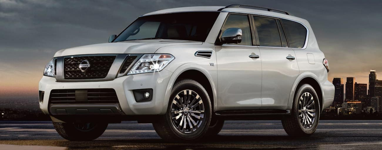 Silver 2019 Nissan Armada at sunset, city skyline in back
