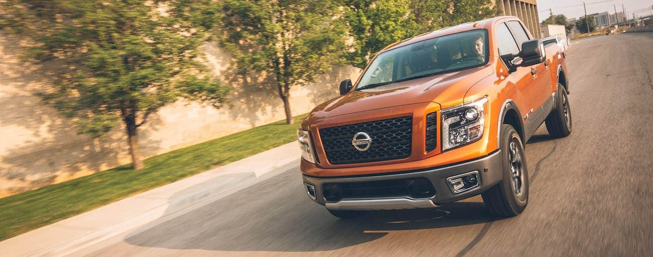 Orange 2019 Nissan Titan driving on tree lined road