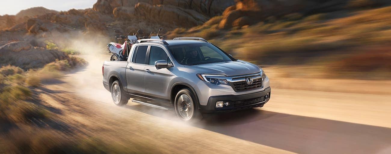 Silver 2019 Honda Ridgeline in desert with dirtbikes in bed