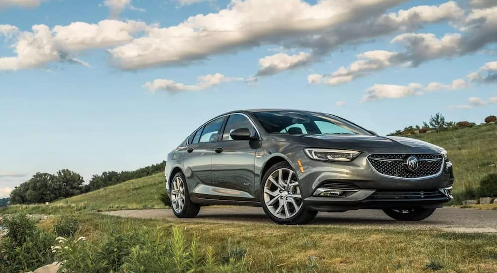 A silver 2019 Buick Regal navigates a twisty grass field lined road