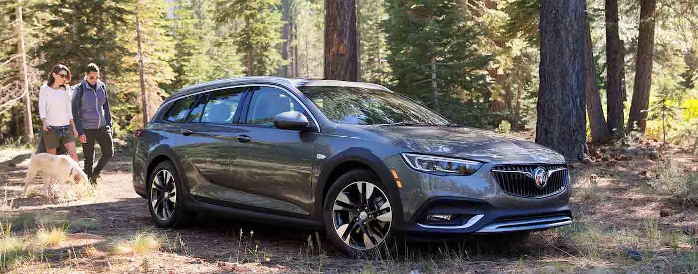 A dark gray Buick Regal on a adventure in the woods