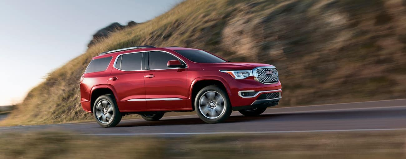 A red 2018 GMC Acadia Denali racing along a mountain road