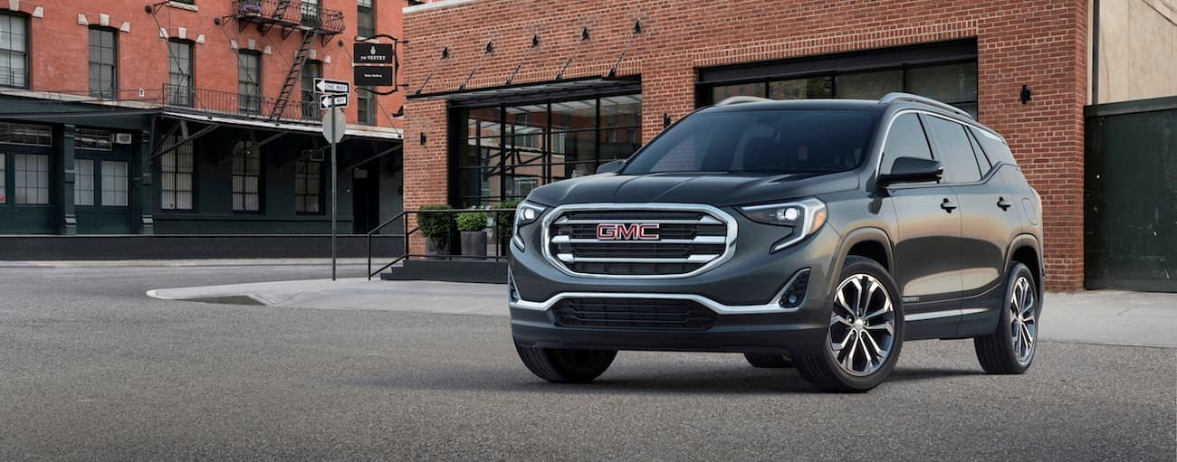 A black 2019 GMC Terrain in front of a brick building