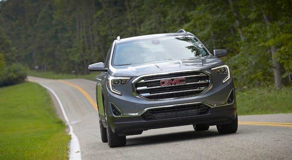 A gray 2018 GMC Terrain driving on a woodland road