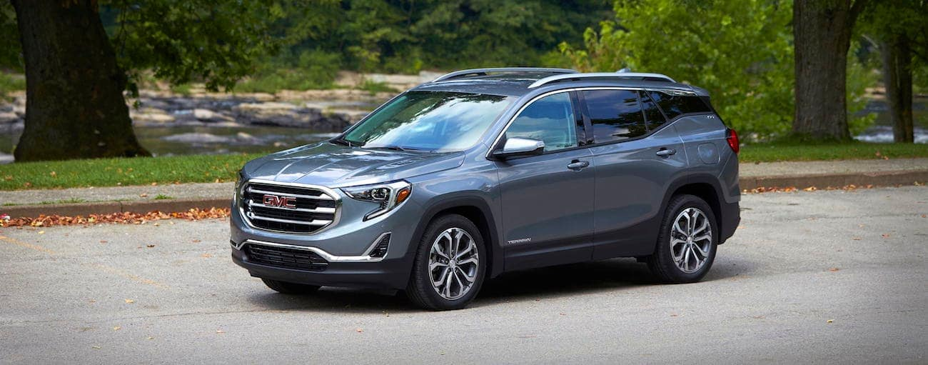 A gray 2019 GMC Terrain drives through a park