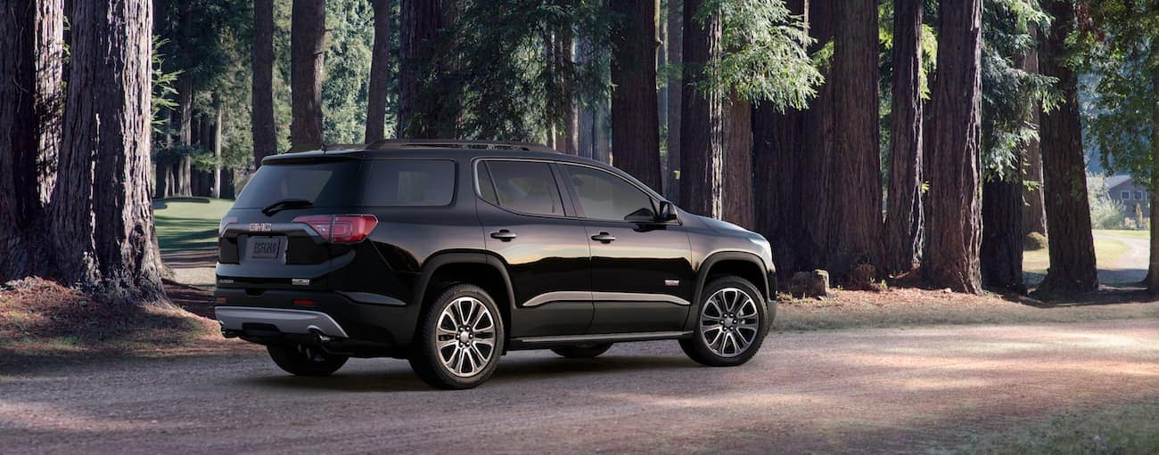A black 2019 GMC Acadia All Terrain in a forest of tall evergreens