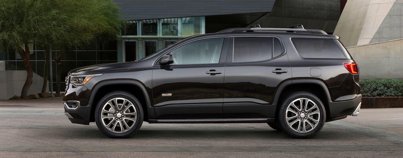 A black 2018 GMC Acadia All Terrain parked in front of a museum-looking building