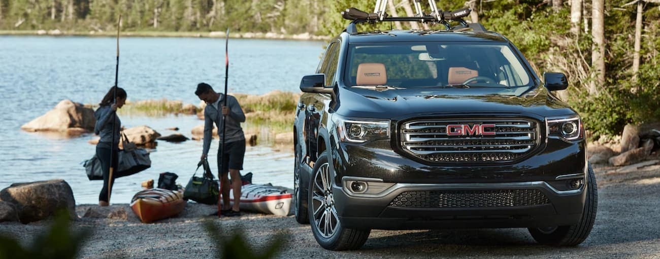A couple unpacks their kayaks at a lake with their black 2019 GMC Acadia