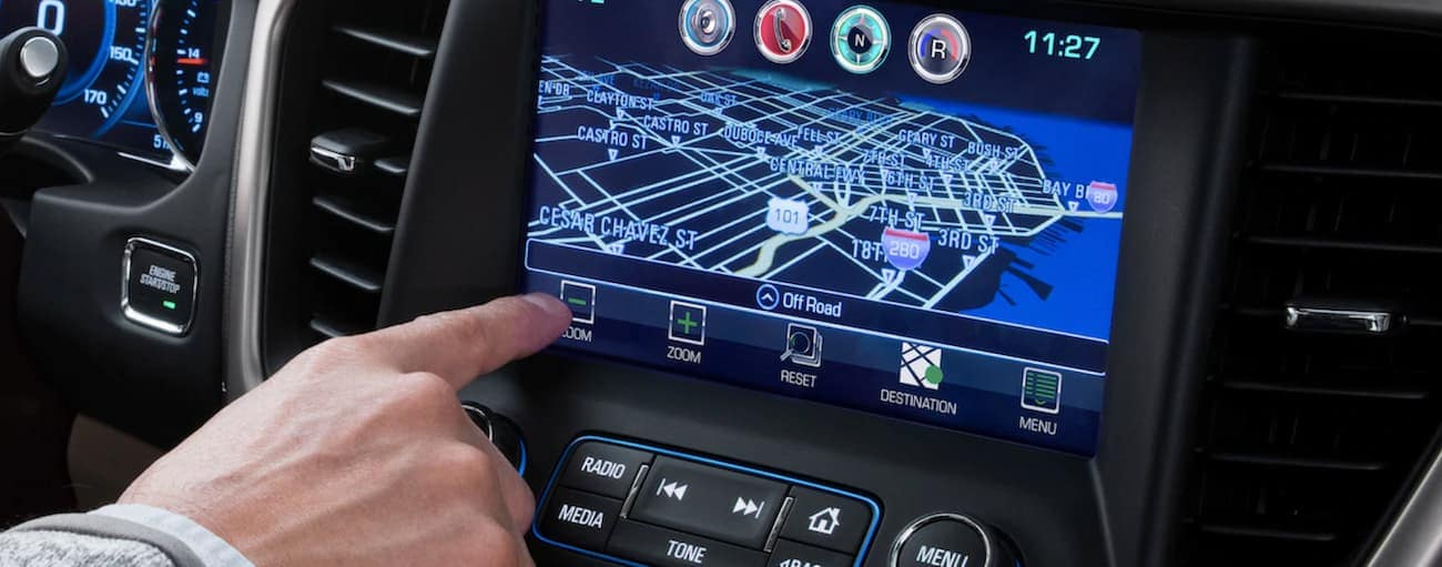 A closeup of a hand pressing buttons on the 2019 GMC Acadia touchscreen