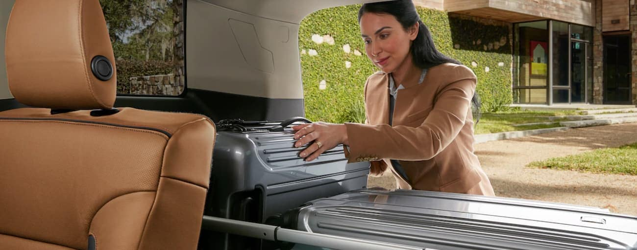 A woman loading cargo into the back of a 2019 GMC Acadia