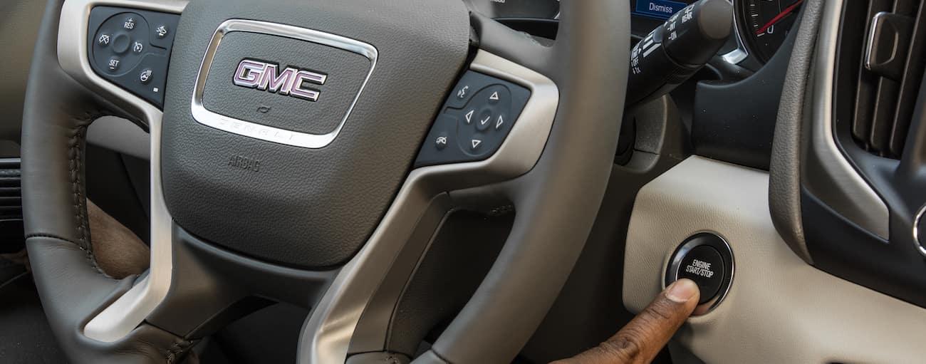 A closeup of the steering wheel and push button start on a 2019 GMC Terrain Denali