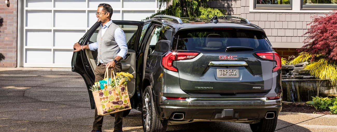 A man walks away from a gray 2019 GMC Terrain with a shopping bag in hand
