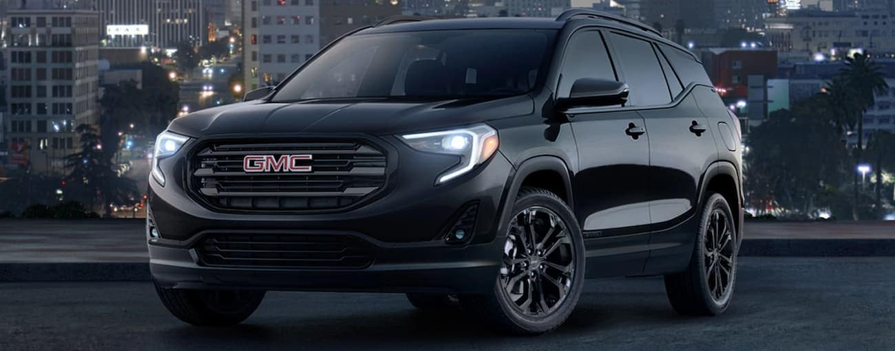 A black 2019 GMC Terrain with a city in the back at night