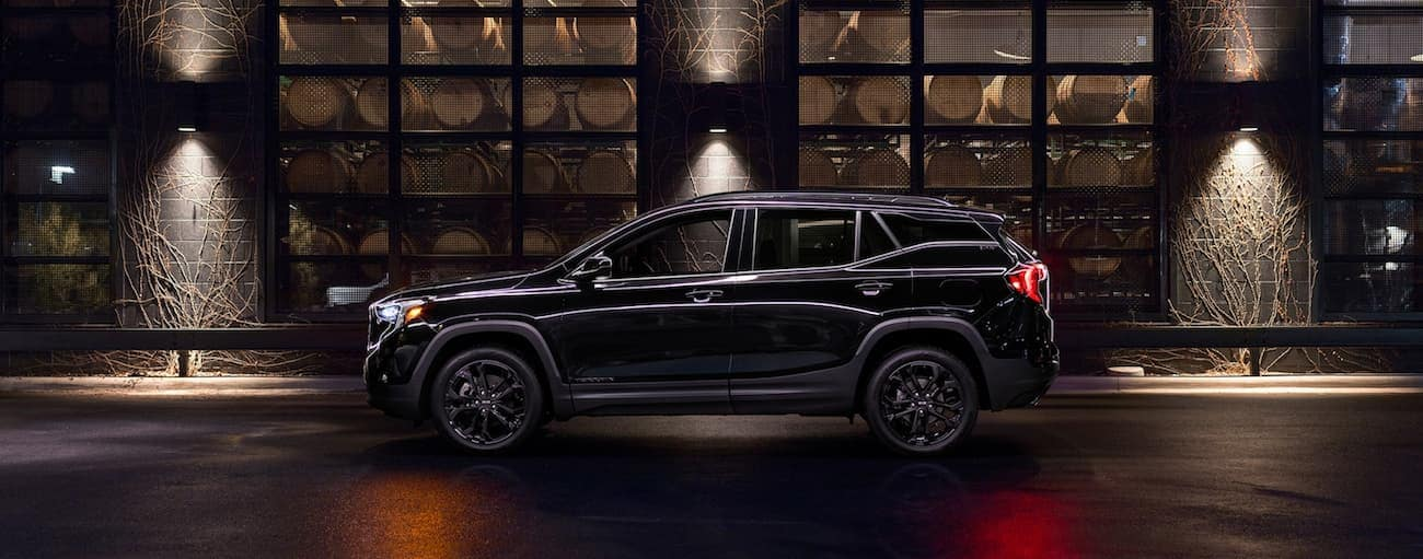 A black 2019 GMC Terrain sits outside a winery at night