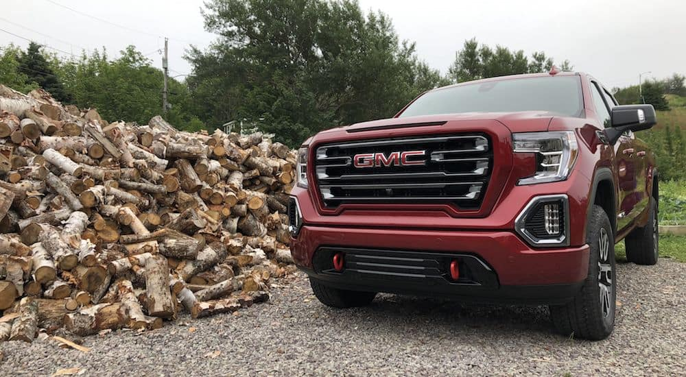 A red 2019 GMC Sierra next to a giant pile of wood