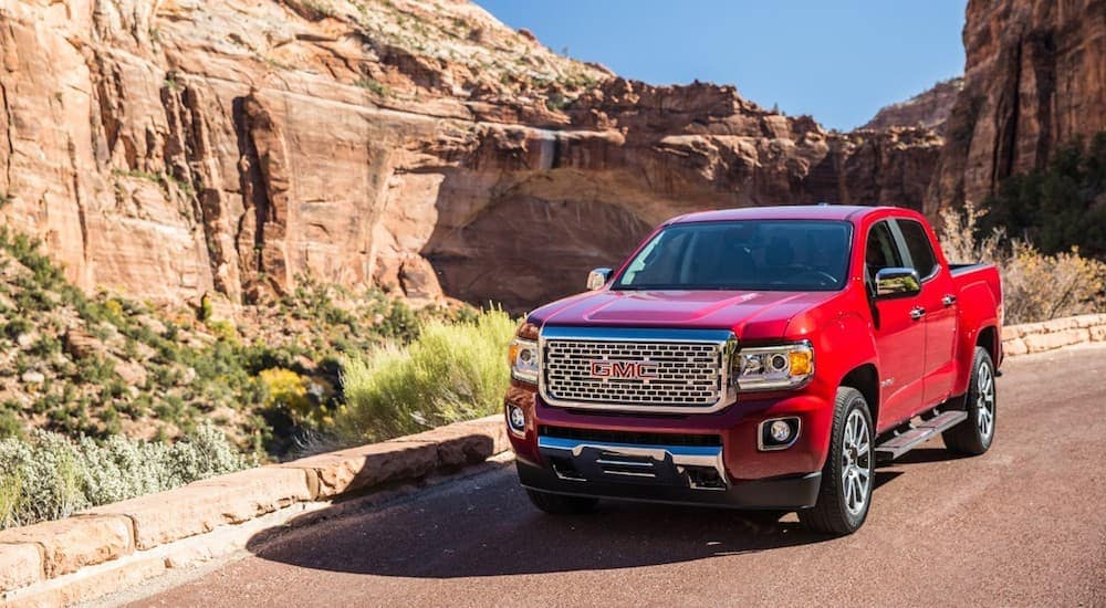 A red 2019 GMC Canyon Denali within a large stone canyon