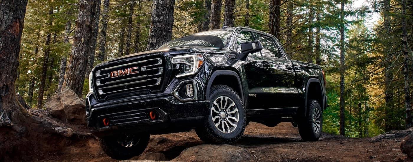 A black 2019 GMC Sierra AT4 navigates a rocky trail