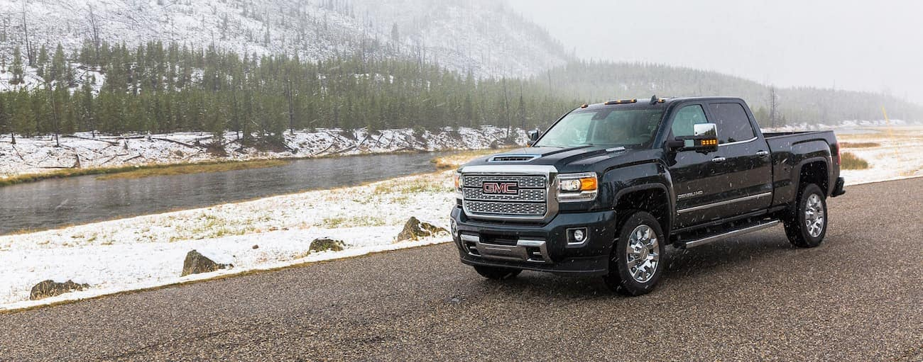 A dark blue Sierra HD Denali in front of a snow-covered mountain after having won 2019 GMC Sierra 2500 HD vs 2019 Ford F-250