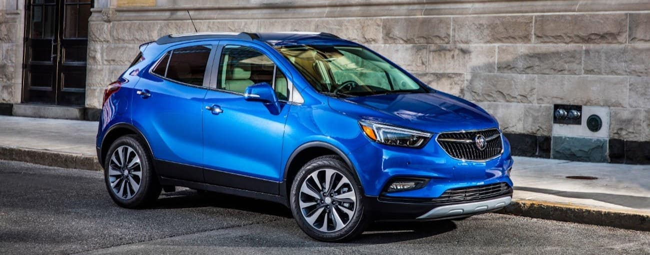 A bright blue 2019 Buick Encore in front of a stone building