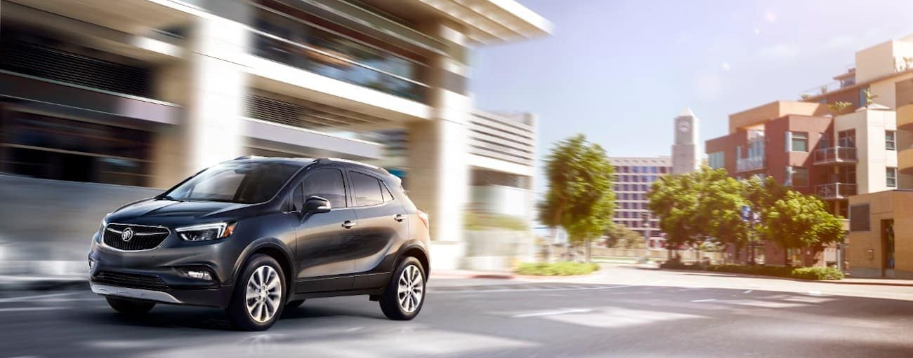 A black 2019 Buick Encore races down a busy city street