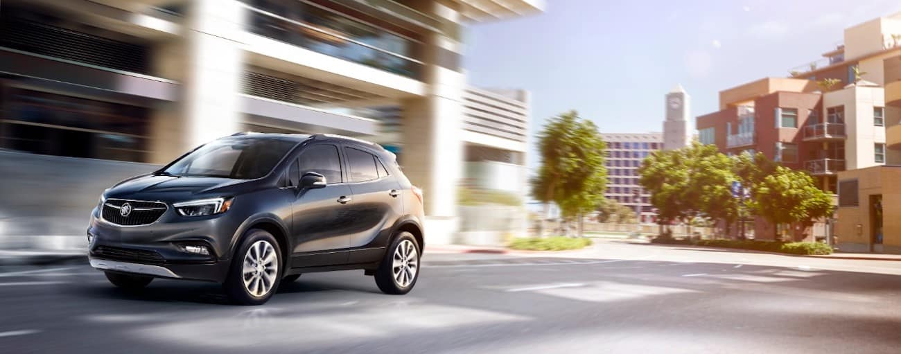 A black 2019 Buick Encore zips down a city side street