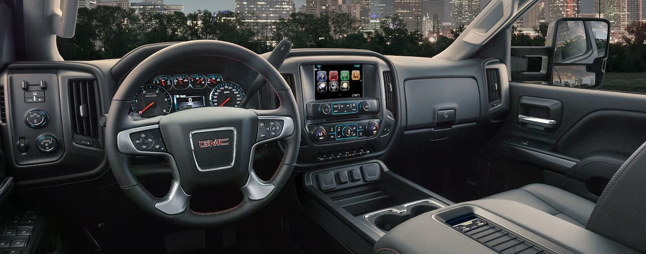 The black interior of a Sierra overlooking a city at night, having won 2019 GMC Sierra 2500 HD vs 2019 Chevy Silverado 2500 HD