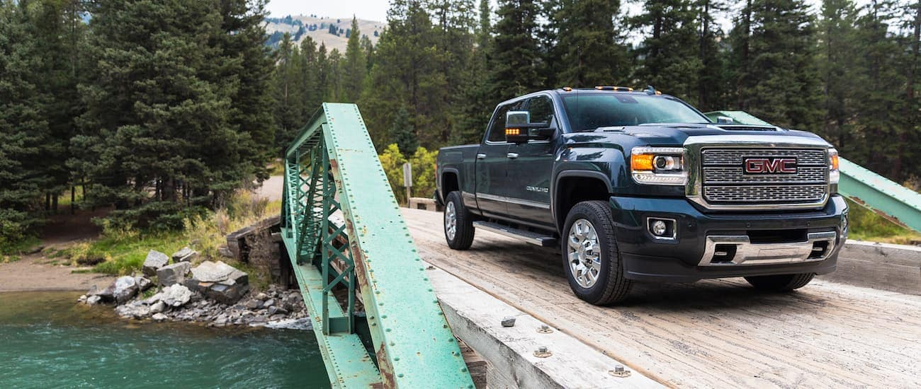 A blue Sierra driving over a bridge in the wilderness after winning 2019 GMC Sierra 2500 HD vs 2019 Nissan Titan XD