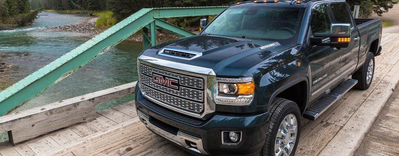 A dark blue Sierra Denali driving over a bridge and away with the win of 2019 GMC Sierra 2500 HD vs 2019 Chevy Silverado 2500 HD