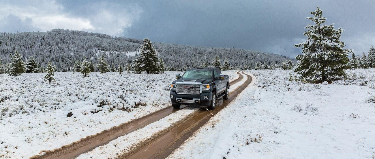 A black Denali drives through a snowy field having won 2019 GMC Sierra 2500 HD vs 2019 Nissan Titan XD