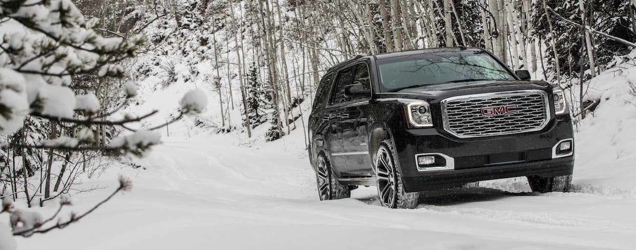 A black Yukon XL Denali tears through the snow and the competition of 2019 GMC Yukon XL vs 2019 Toyota Sequoia
