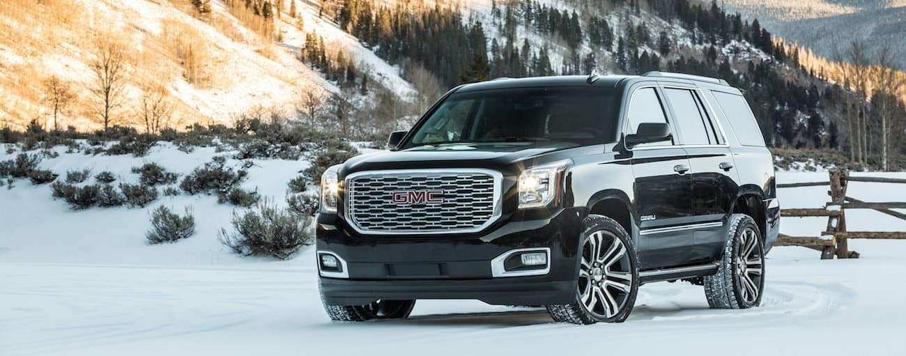 A black Denali stands victorious with a snow-covered mountain after winning 2019 GMC Yukon XL vs 2019 Ford Expedition EL