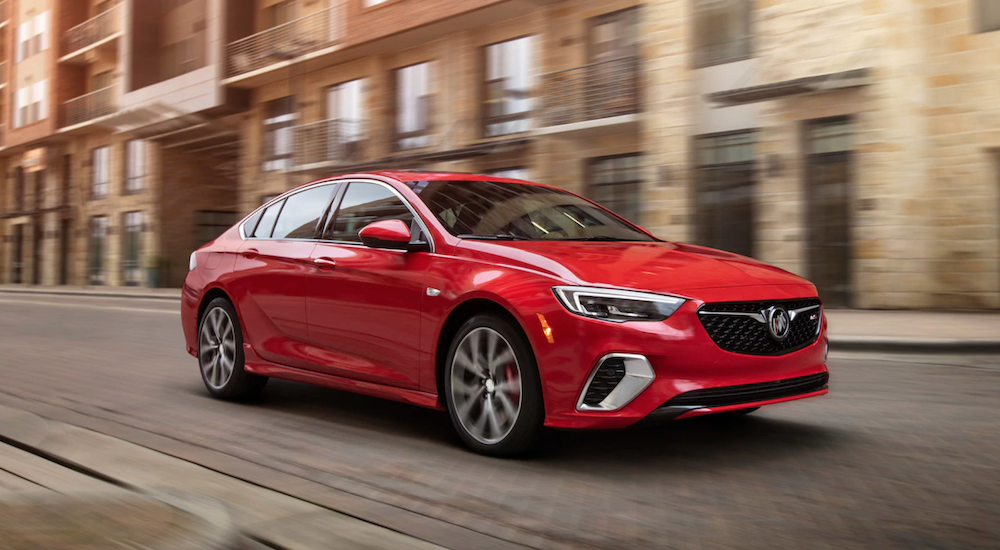 A red 2019 Buick Regal GS is driving down city block. They can be found at several Buick dealers in GA.