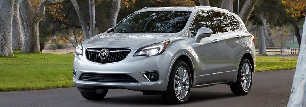 white 2019 Buick Envision driving down tree-lined street