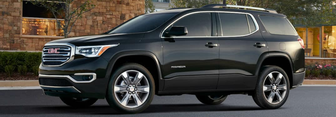 2019 GMC Acadia exterior front fascia and driver side in front of brick building