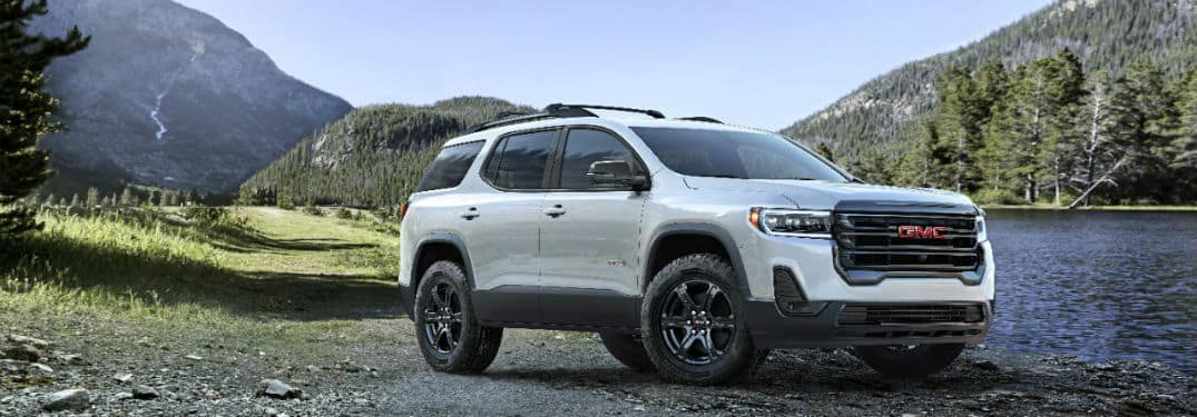 2020 GMC Acadia AT4 exterior front fascia and passenger side in valley between mountains